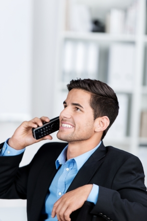 cordless: Happy young businessman using cordless phone while looking up in office