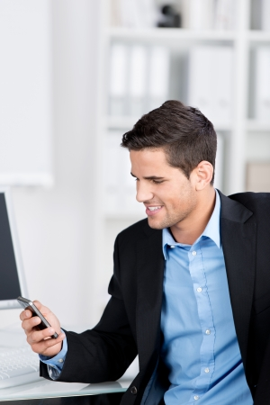 Handsome stylish young businessman smiling while looking at a message on the screen of his mobile phone while seated at his desk in the office photo