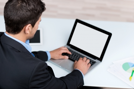 paper screens: High view rear view of young businessman using laptop at desk in office