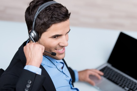 helpline: Happy young male customer service executive conversing on headset at desk in office Stock Photo