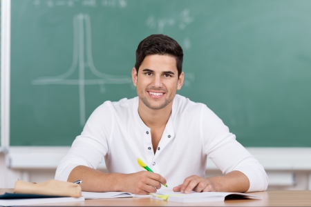 scholar: Happy handsome young male university student sitting in front of a blackboard at his desk taking notes looking up at the viewer with a lovely smile Stock Photo