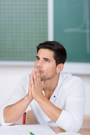 Thoughtful young male student with hands clasped looking away in classroom photo