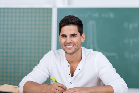Portrait of happy young male student in classroom photo