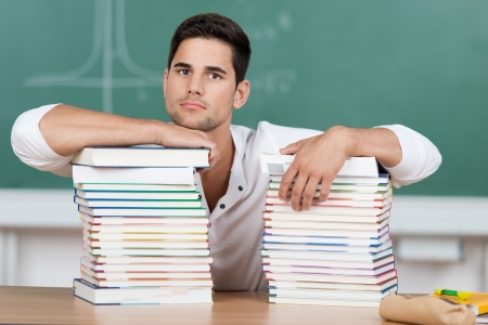 Serious handsome young male student student with two high piles of textbooks in front of him resting his chin on top of one stack with a grim expression from overwork and pressure photo