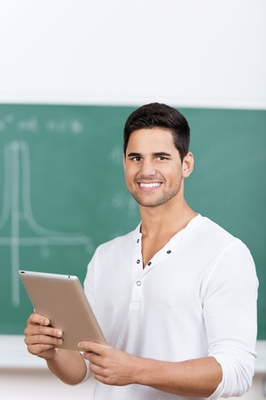 Portrait of happy young male student holding digital tablet in classroom photo