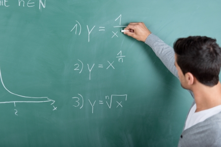 Male teacher with his back to the camera writing a mathematical formula on the blackboard in a classroom while teaching a class Stock Photo