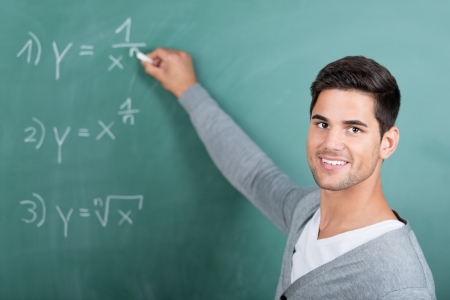 sums: Portrait of happy young male student solving sums on chalkboard in classroom