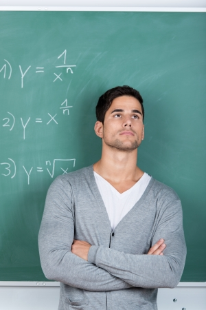 Thoughtful man standing with his arms folded in front of the chalkboard in a classroom with mathematical equations staring off into the distance photo