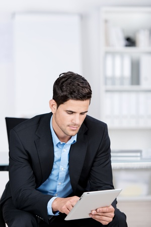 Handsome caucasian businessman sitting in a chair by the office, and working with a tablet photo