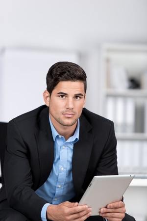 Serious handsome businessman holding a tablet computer in his hands leaning forwards looking at the camera with an earnest expression photo