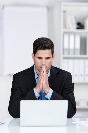 dudas: Joven hombre de negocios con las manos juntas usando la computadora portátil en el escritorio en la oficina Foto de archivo