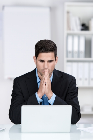 Young businessman with hands clasped using laptop at desk in office