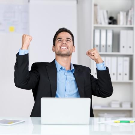 Succesvolle zakenman vreugde hief zijn gezicht naar de hemel en ponsen de lucht met zijn vuisten als hij zit aan zijn bureau in het kantoor Stockfoto
