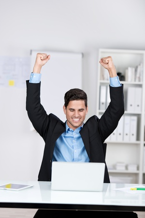jubilation: Jubilant businessman sitting in front of his open laptop with his fists raised in the air and a beaming smile of success