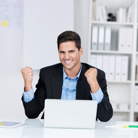 Portrait of happy young businessman with laptop celebrating victory at desk in office Stock Photo