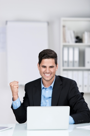 jubilation: Jubilant businessman rejoicing smiling broadly and punching the air with his fist as he reads information on his laptop screen