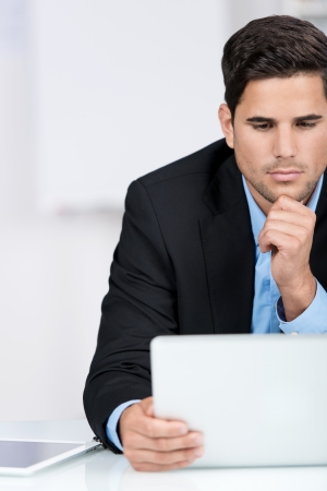 Businessman reading interesting news on his laptop sitting looking at the screen with an earnest expression, partial closeup portrait photo