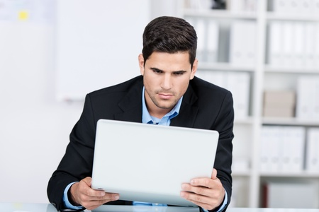 portable failure: Curious young businessman holding laptop at desk in office