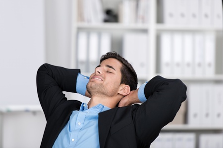 lean back: Relaxed young businessman with hands behind head in office
