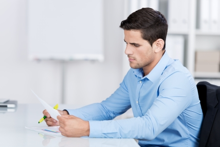shirtsleeves: Businessman reading a document while sitting at his desk in the office looking at it with a serious expression