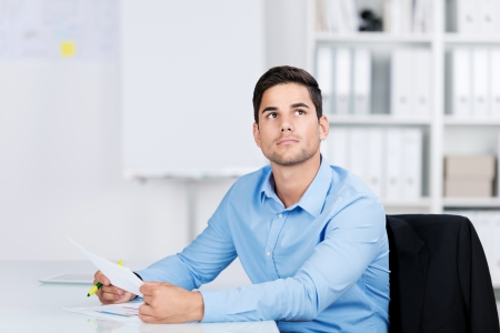 shirtsleeves: Young man daydreaming in the office sitting at his desk with a document in his hands staring up into space lost in thought Stock Photo