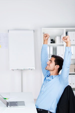 Young and cheerful businessman raising his arms in the air inside office celebrating after making a successful deal or project. photo