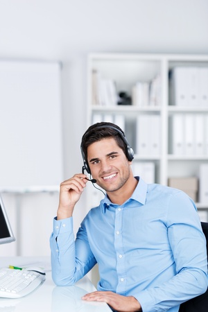 Portrait of confident young male customer service executive communicating on headset at desk in office photo