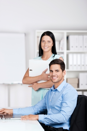 Businesswoman and businessman working in the same office, looking at the camera and smiling. photo