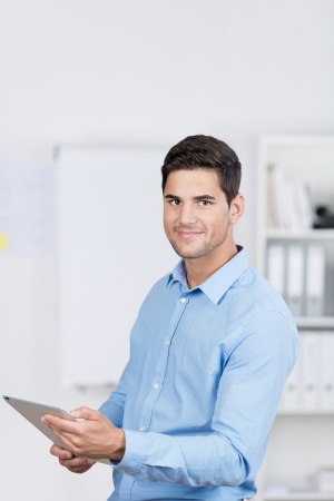 pda: Handsome caucasian businessman standing in the office, and working with a tablet