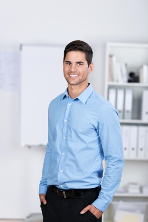 Portrait of confident young businessman with hands in pockets standing in office photo