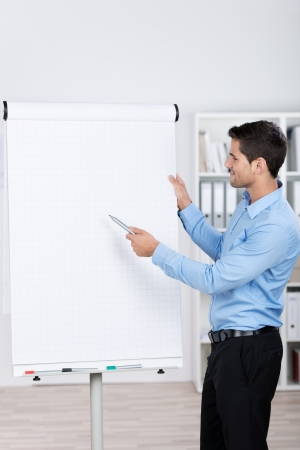 Young businessman standing near a flipchart and explaining the numbers. photo