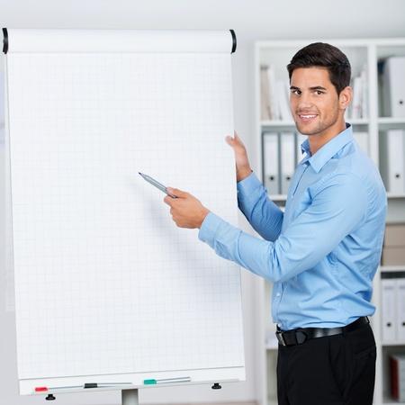 Hombre de negocios joven que presenta los datos importantes en un rotafolio con una sonrisa.