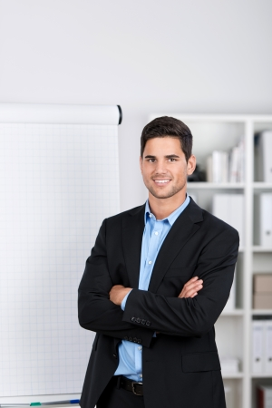 Smiling handsome caucasian businessman standing by the side of a blank flip-chart in the office photo