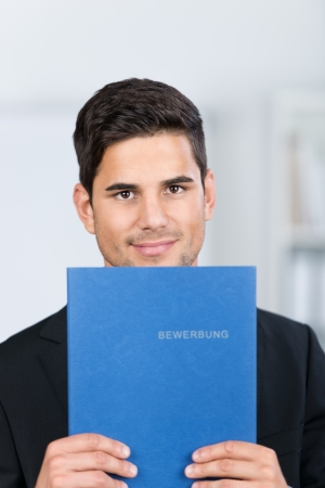Portrait of confident young businessman holding application file in office photo