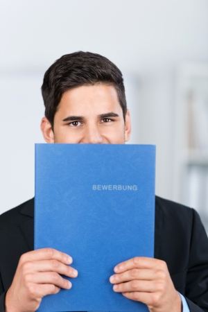 timid: Young male business executive holding a file of application portfolio in front of his face in the office. Stock Photo
