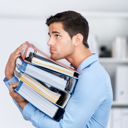 overloaded: Side view of young businessman carrying stacked binders in office Stock Photo