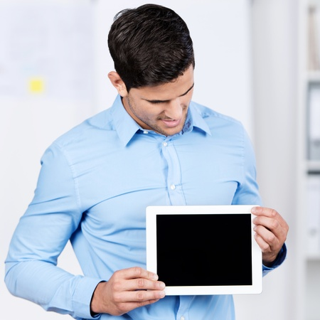 Young businessman holding digital tablet while looking at it in office photo