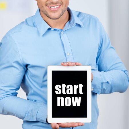 Midsection of businessman holding digital tablet with Start Now sign in office photo