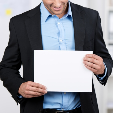 blank area: Closeup of a young businessman showing a blank white sheet.