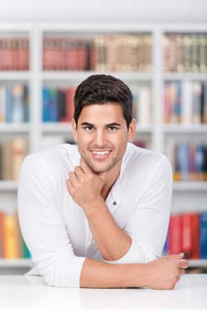 Portrait of confident male student leaning on desk in library photo