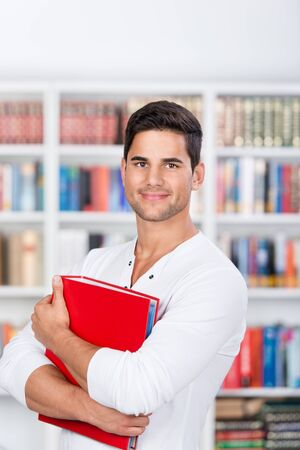 Portrait of confident male student holding binder in library photo