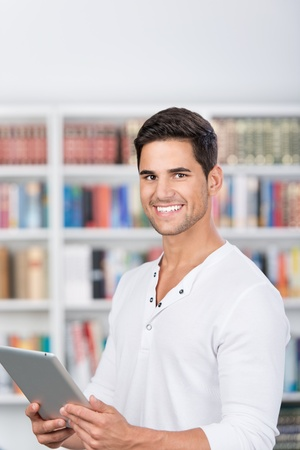 Smiling portrait of a man holding a tablet in front of the bookshelf. photo