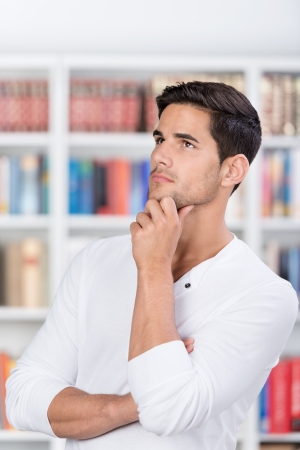 Thoughtful male student with hand on chin looking away in library photo