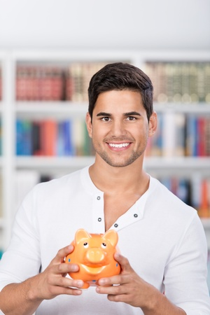 Portrait of male student holding piggybank in library photo