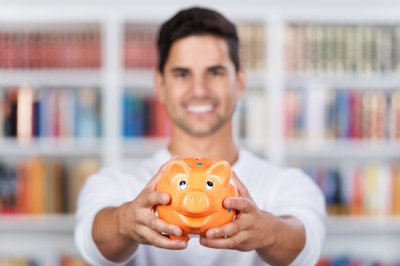 fees: Closeup of a smiling young man showing a piggy bank in the library. Stock Photo