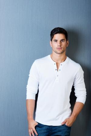 poses de modelos: Retrato de hombre joven en casuals con las manos en los bolsillos contra la pared azul Foto de archivo