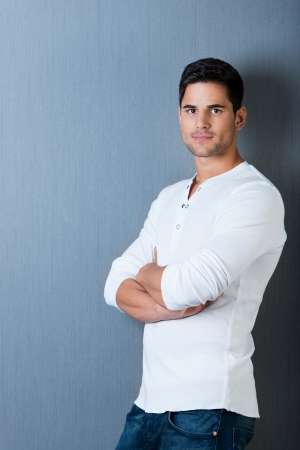 Profile portrait of a handsome male standing leaning on the wall with arms crossed, isolated on blue background. photo