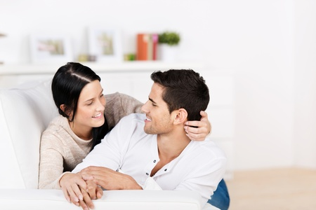 enraptured: Loving attractive young couple cuddling on the sofa staring into each others eyes with tenderness Stock Photo