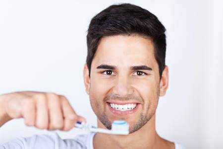 clenching teeth: Closeup portrait of young man brushing teeth at home Stock Photo