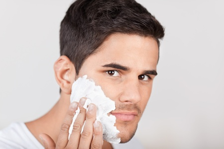 Closeup portrait of a handsome young Latino man applying shaving cream to his face photo